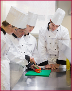 Culinary students learning how to chop vegetables in the kitchen